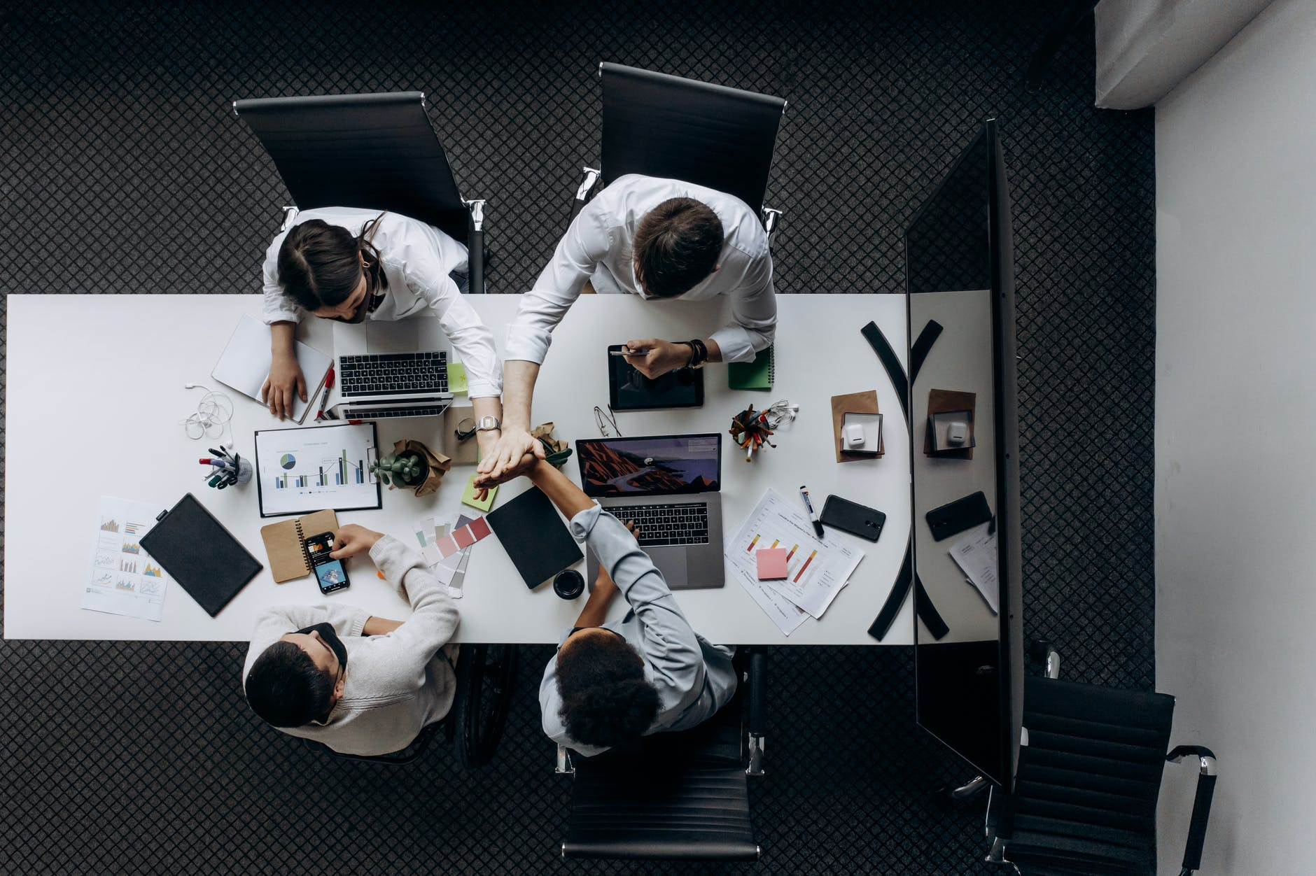 Industries AI Will Disrupt includes Wall Street. A group of men sit around a boardroom table with a large screen TV at the end. Everyone has phones and laptops and they are looking at charts and graphs