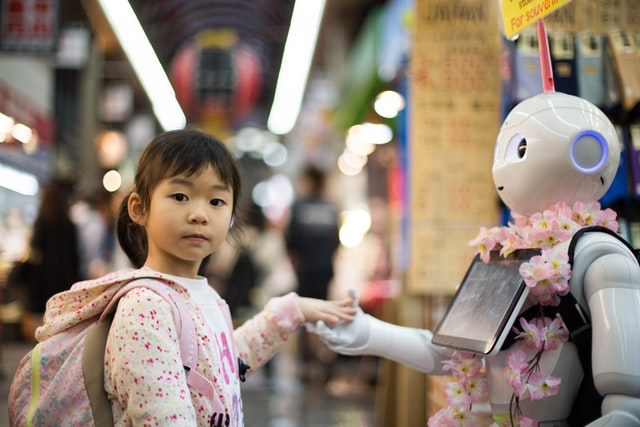 A young girl with black hair and a pink sweater and backpack stands on the left side of the frame, in front of a blurry urban scene. The girl stares straight at the camera with a content expression on her face.   On the right side of the frame a friendly looking white robot, about the same height as the girl, stands facing her, with its hand outstretched towards her. The robot has a touchscreen tablet device mounted on its chest, and it has pink and white flower garlands around its neck.  The girl rests her left hand on top of the robot's outstretched hand.  Could be a mental health chatbot